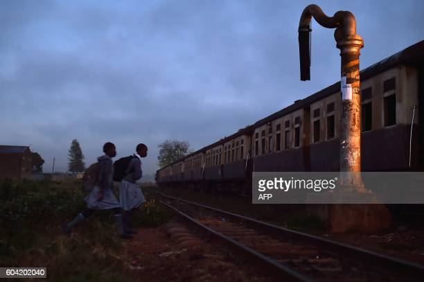 TOPSHOT Two school girls walk towards a commuter train in Kikuyu Kenya on September 13 2016 The railway in Kenya has a long history with the British...