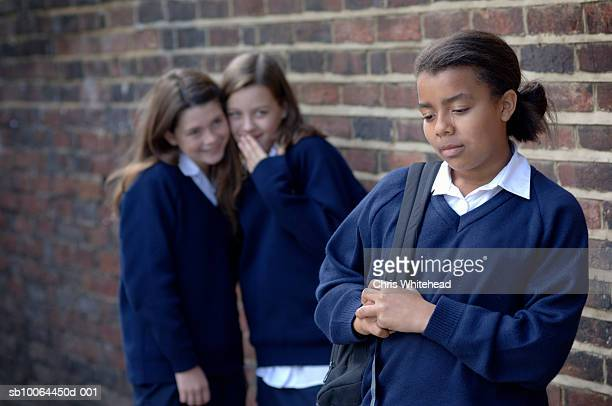 Two school girls (11-12) whispering and laughing at another girl (12-13), focus on front girl