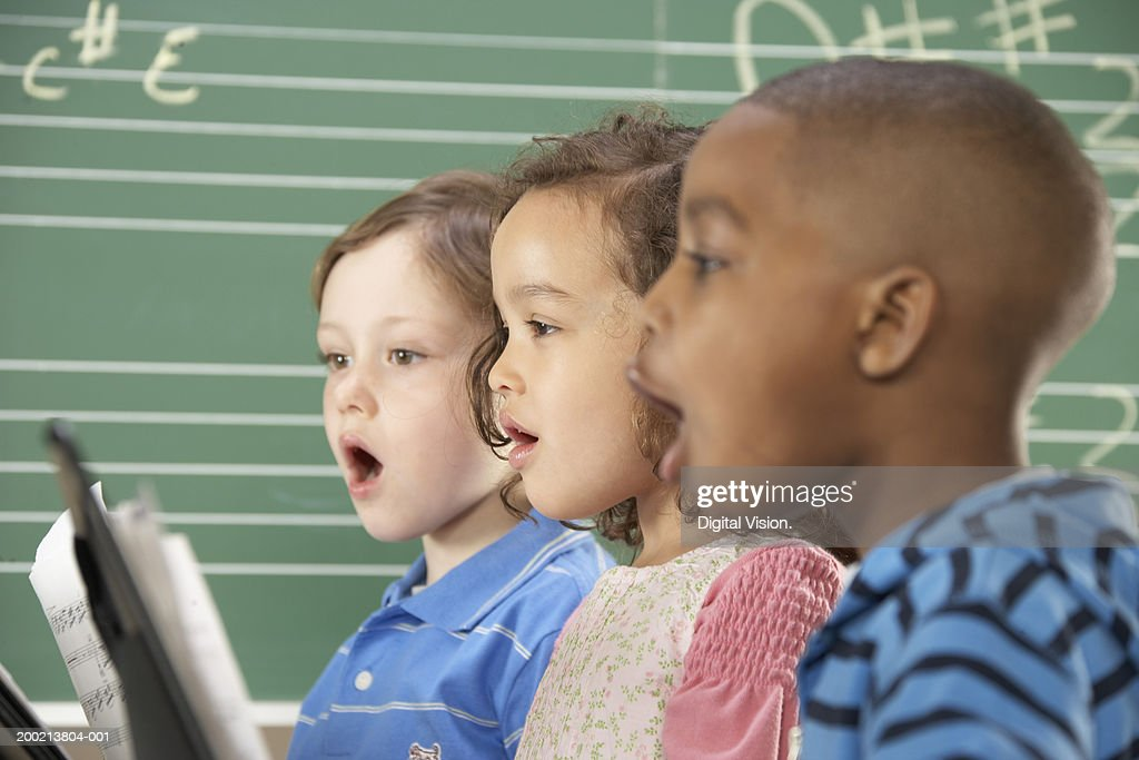 Two schoolboys (5-10) and schoolgirl (5-10) singing in class, close-up : Stockfoto