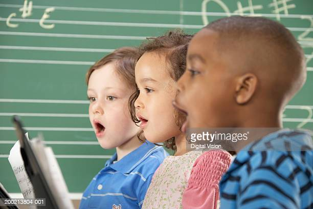 Two schoolboys (5-10) and schoolgirl (5-10) singing in class, close-up