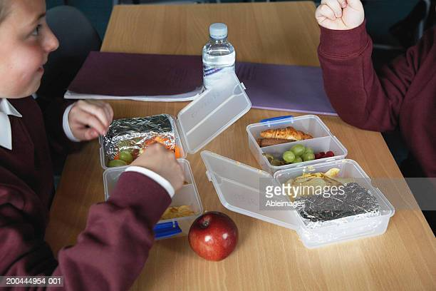 Two schoolboys (8-10) eating lunch at table, close-up