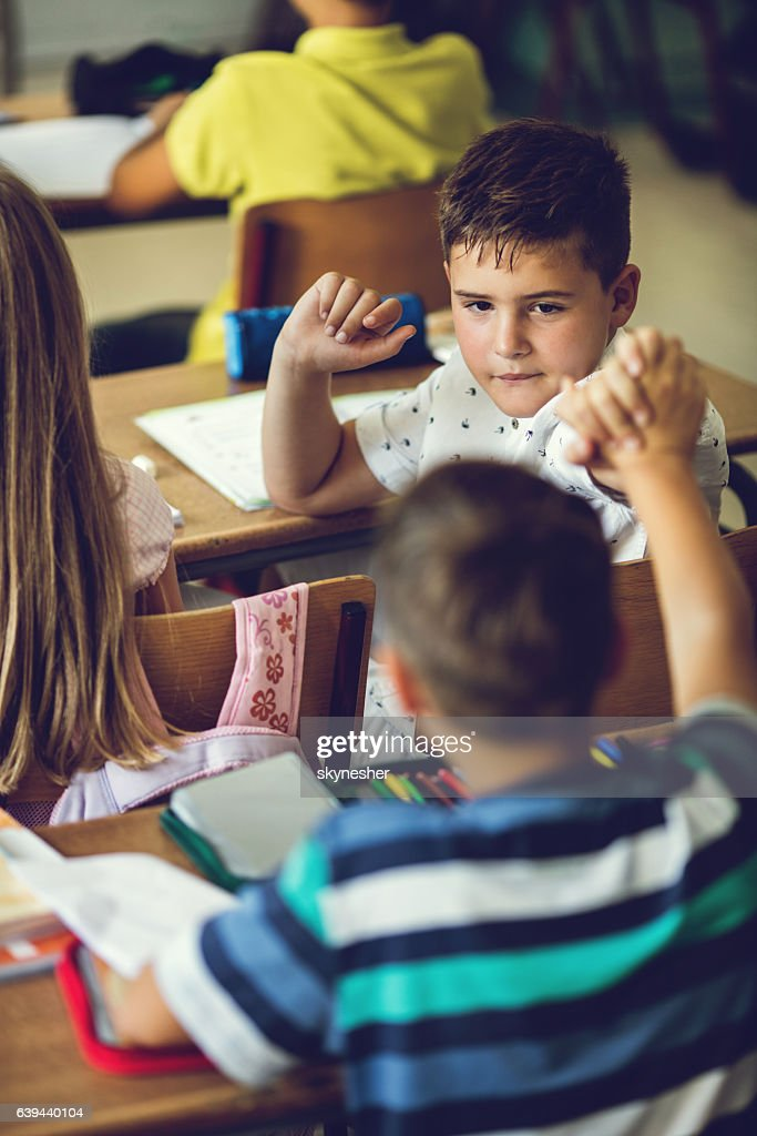 Two schoolboys greeting while sittig at the desk in classroom stock two schoolboys greeting while sittig at the desk in classroom stock photo m4hsunfo