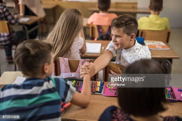 Twee schooljongens groet zittend in de klas.