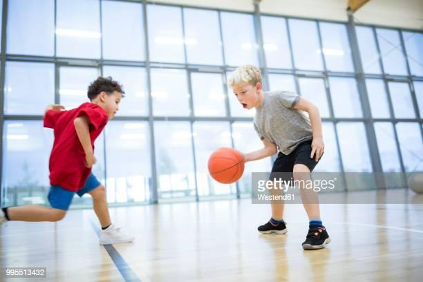 two schoolboys playing basketball in gym class - sporting term - fotografias e filmes do acervo