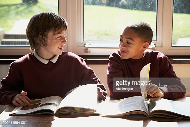Two schoolboys (9-12) sitting in class turning pages in books, smiling