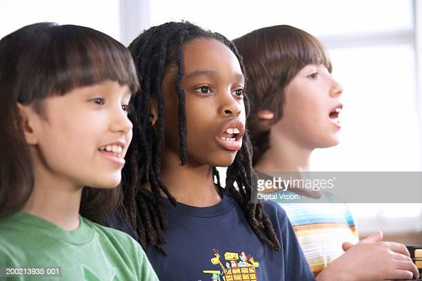Two schoolgirls and schoolboy (6-12) singing in row, close-up