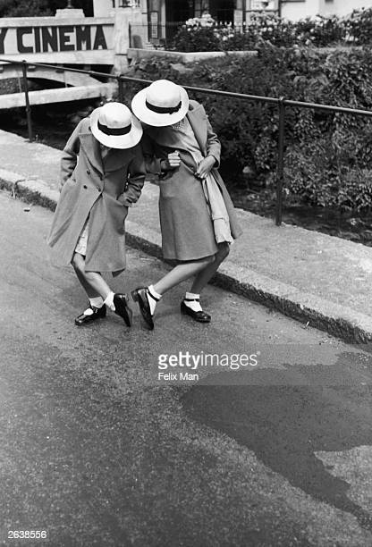 Two schoolgirls comparing their shoe sizes Original Publication Picture Post 3 The Life Of A Village pub 1938