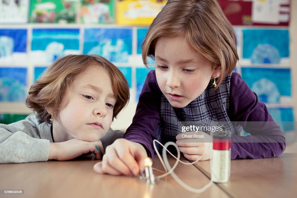 Two schoolgirls (6-7) experimenting with electricity in science class : Foto de stock