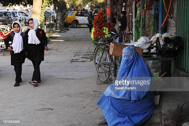 Two schoolgirls in veil and uniform go past a woman in a burka sat on a step on the pavement on October 19, 2011 in Kabul, Afghanistan.