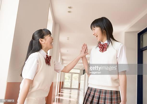 Two schoolgirls laughing in corridor