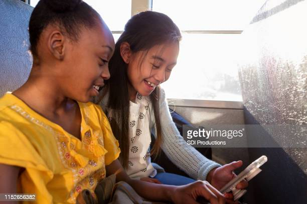 二人の女子学生は一緒に携帯電話を見て - 乗り物に乗って ストックフォトと画像