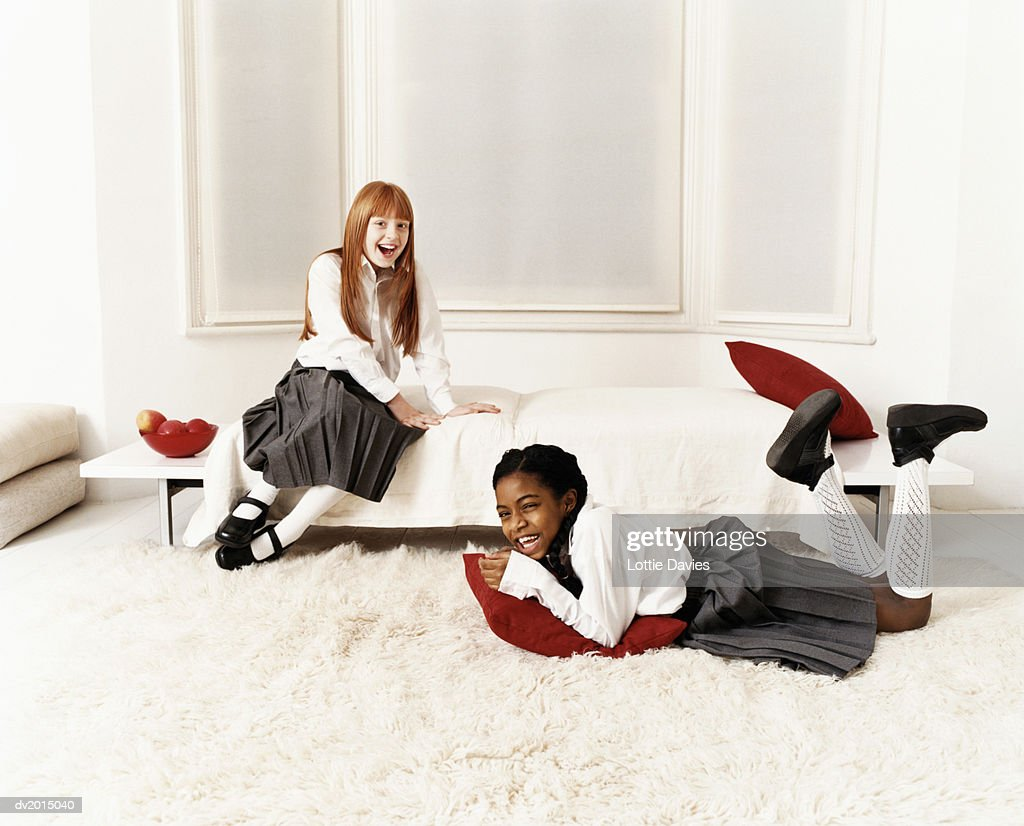 Two Schoolgirls Messing About in a Living Room : Stock Photo