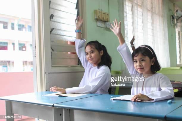zwei schülerinnen heben ihre hände in einem klassenzimmer - schulkind nur mädchen stock-fotos und bilder