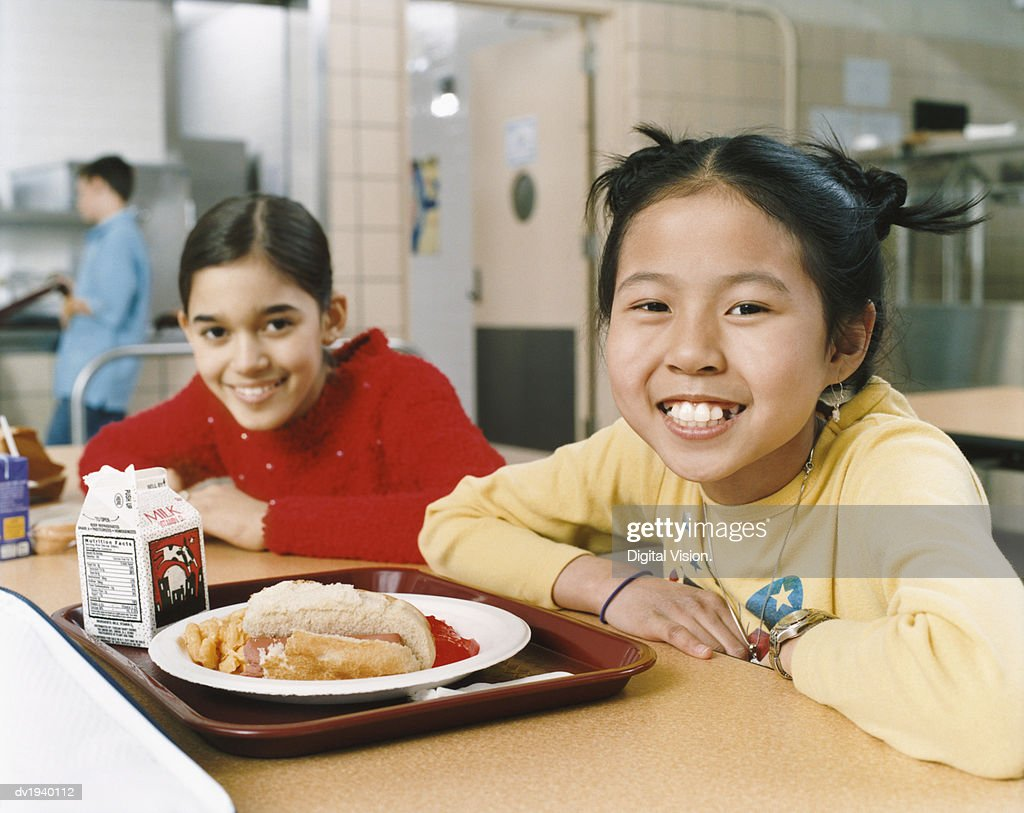Two Schoolgirls Sit at a Table in a Canteen : Stock Photo