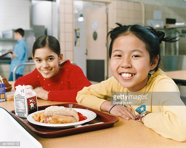 two schoolgirls sit at a table in a canteen - milk carton stock photos and pictures