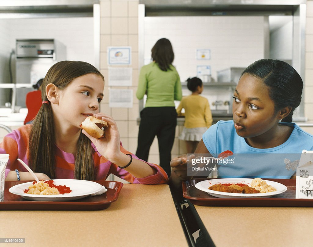 Two Schoolgirls Sitting at a Table in a Canteen Eating Their Lunch : Stock Photo