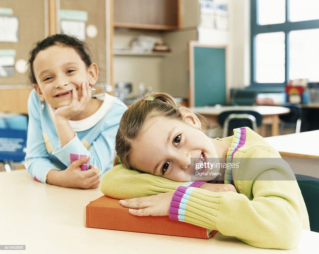 Two Schoolgirls Sitting at Their Desks in a Classroom at Primary School : Stock Photo