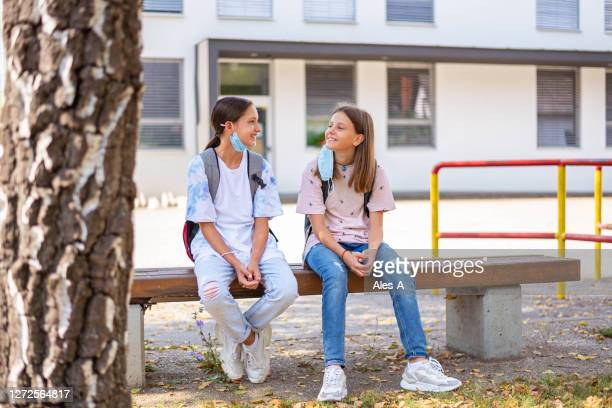 two schoolgirls sitting on a bench and wearing face masks under the chin - mistake stock pictures, royalty-free photos & images