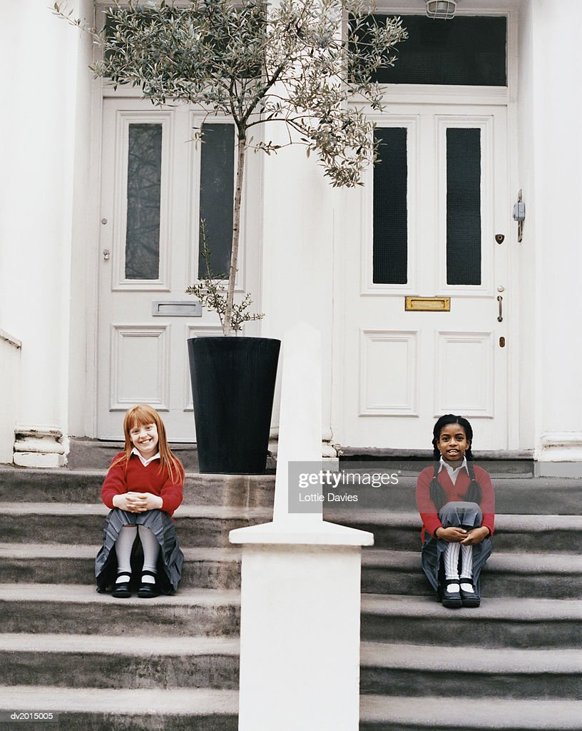 Two Schoolgirls Sitting on Steps In Front of Their Houses : Stock Photo