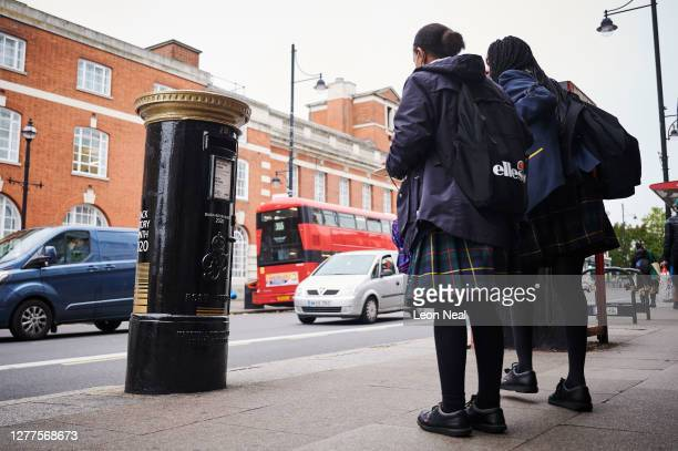 Two schoolgirls stop to look at one of four postboxes painted black to honour black Britons on September 30, 2020 in London, England. Decorated to...