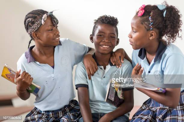 Two Schoolgirls with a bow in their hair and school uniform smiling together with a schoolboy in their classroom in a catholic school located in El...