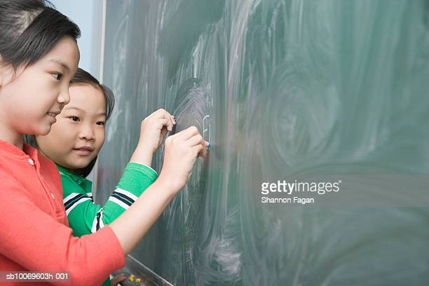 Two schoolgirls (8-9) writing on  blackboard, smiling
