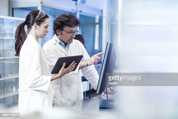 two scientist looking at the computer monitor - science and technology stock pictures, royalty-free photos & images