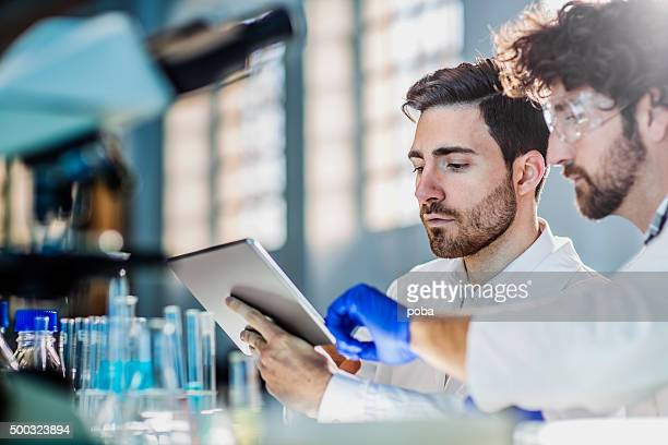 two scientist using digital tablet in laboratory - medicinsk forskning bildbanksfoton och bilder