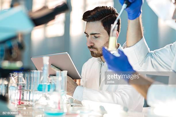 Deux scientifiques à l'aide de tablette numérique en laboratoire