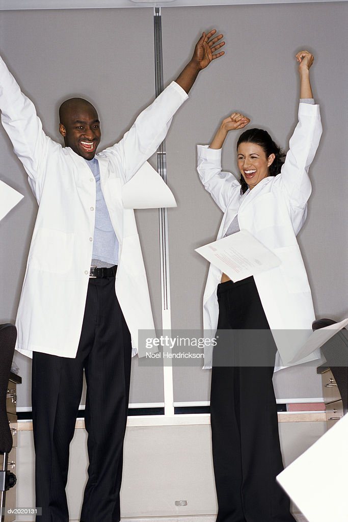 Two Scientists Celebrating With Upstretched Arms in the Laboratory : Stock Photo