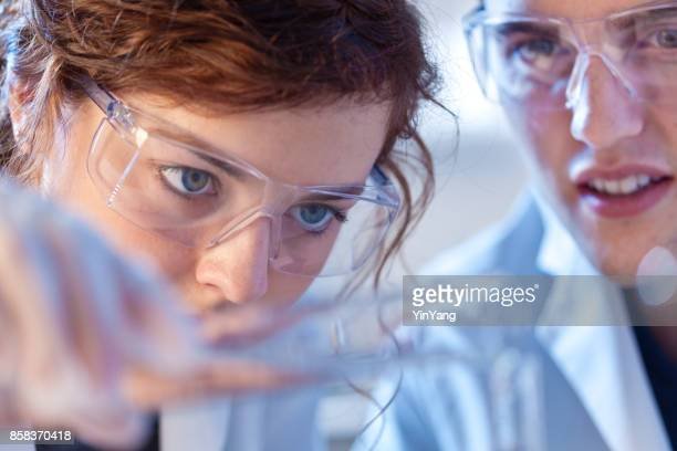 two scientists chemist working together in a laboratory in a chemical solution - bioquímico imagens e fotografias de stock
