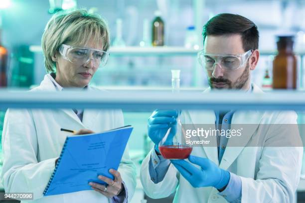 Two scientists cooperating while examining liquid in laboratory.