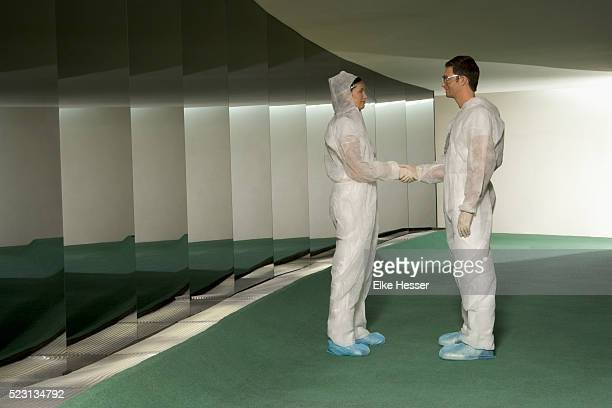two scientists in protective suit shaking hands - schutzanzug stock-fotos und bilder