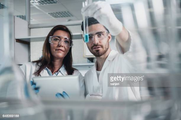 Two Scientists Looking at a Test Tube Filled With a Reagent