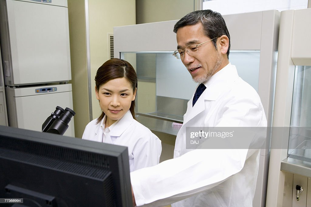 Two scientists talking and looking at a computer monitor, front view, side view : Stock Photo