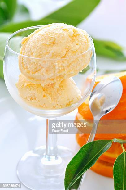 Two scoops of orange ice cream in a glass