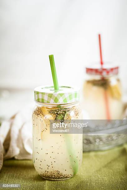 Two screw-top jar of chia fresca, mexican lemonade with chia seeds, Salvia hispanica, and mint