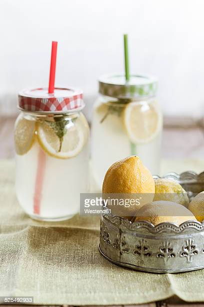 Two screw-top jars of lemon and mint infused water and a bowl of lemons