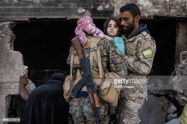 Two SDF fighters are helping a young girl flee the centre of Raqqa The girl lost her parents and she was in Trauma The Syrian civil war has been...