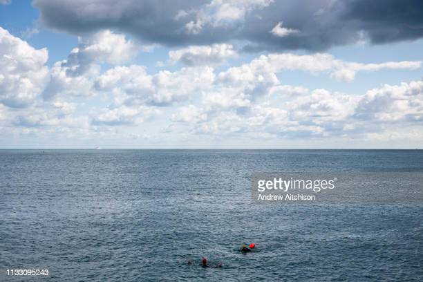 Two sea swimmers return to Folkestone harbour after a training session out in the English Channel Folkestone Kent England United Kingdom