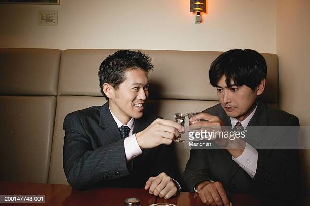 Two seated businessmen toasting glasses