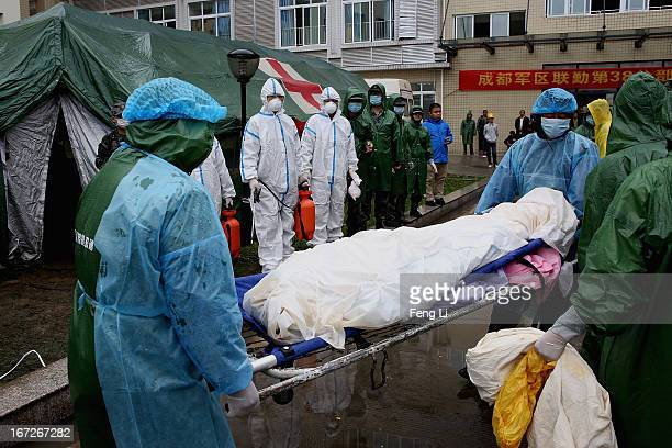 Two security guards carry the dead body of a victims at a hospital on April 23 2013 in Lushan county of Ya An China A magnitude 7 earthquake hit...
