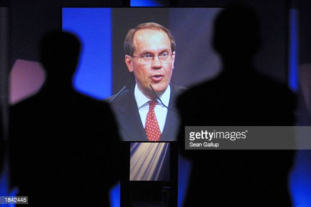 Two security guards cast their silhouette in front of a video screen showing the opening speech by Nokia CEO Jorma Ollila of the CeBIT technology...
