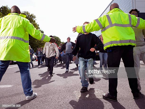 Two security guards holding out arms to stop advancing crowd