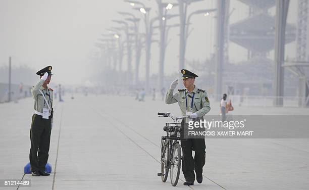 Two security guards salute each others as a thick haze of heat, dust and pollution is seen in the Olympic green area during the China Athletics Open...