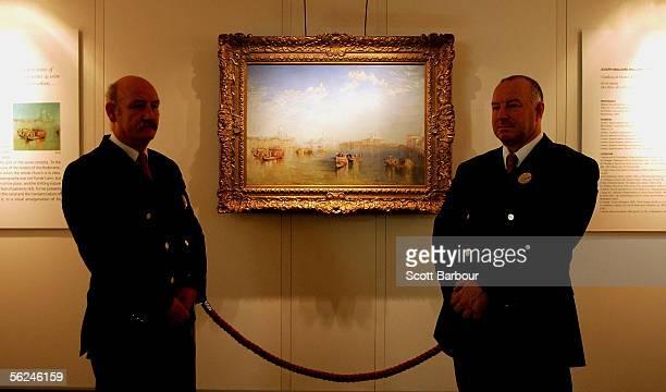 Two security guards stand near JMW Turner's masterpiece 'Giudecca La Donna della Salute and San Giorgio' at Christie's auction house on November 21...