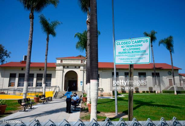 Two security guards talk on the campus of the closed McKinley School, part of the Los Angeles Unified School District system, in Compton, California,...
