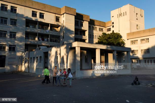 Two security guards walk past a group of children who are amongst some of the people living illegally in the deserted Helen Bowden Nurses home in the...