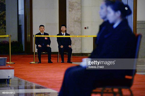 Two security guards watch on ahead of upcoming opening sessions of the Chinese People's Political Consultative Conference and the National People's...