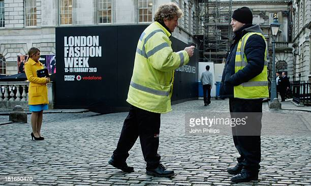 Two security men wearing yellow hi-vis jackets talk animatedly at the entrance to London Fashion Week, held in the courtyard of Somerset House. In...